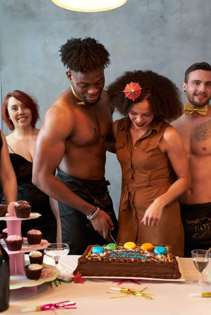 A naked butler cutting a cake with the birthday girl